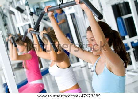 beautiful women at the gym doing exercises on a machine - stock photo