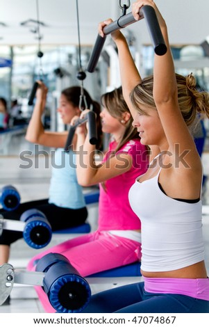 Beautiful women at the gym exercising on machines