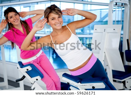 Beautiful women at the gym exercising on the machines - stock photo