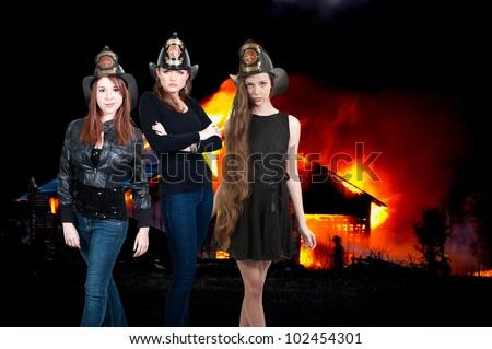 Beautiful women firefighters at a blazing fire - stock photo