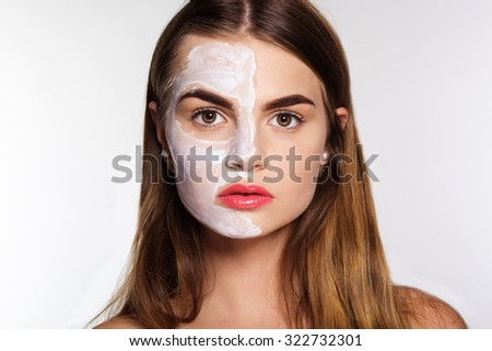 Beautiful women getting white clay facial mask on half part of face, isolated on white - stock photo