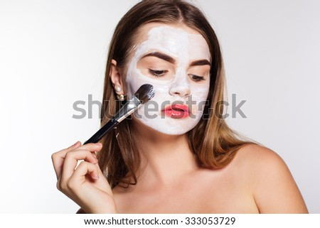 Beautiful women getting white clay facial mask on her face - stock photo