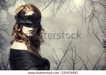 Beautiful women in carnival mask. Photo with forest at background. - stock photo