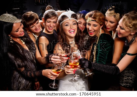 Beautiful women in evening dresses with champagne glasses - stock photo
