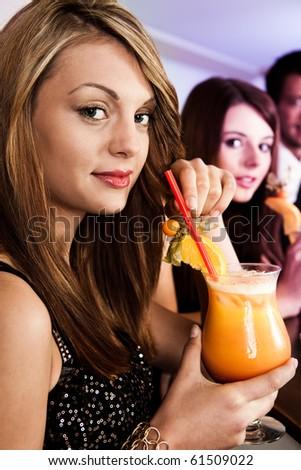 Beautiful women in nightclub with tequila sunrise - stock photo