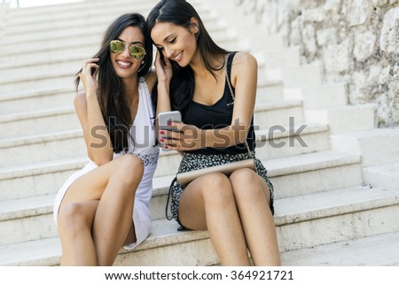 Beautiful women looking at phone and smiling while reading the contents