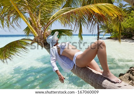 Beautiful women lying on the branch of palms tree