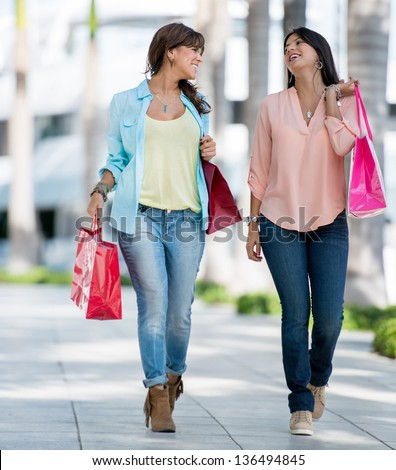 Beautiful women on a shopping spree carrying bags - stock photo