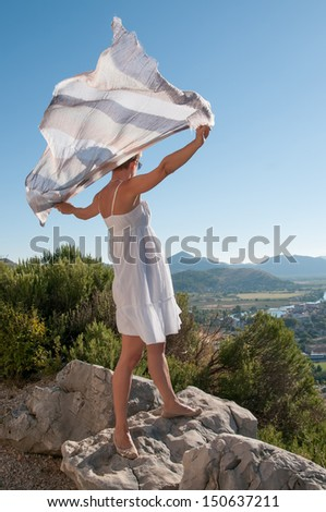 Beautiful women on the hill plays with a scarf