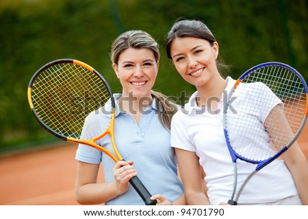 Beautiful women playing tennis and looking happy