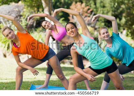 Beautiful women practicing yoga in park - stock photo