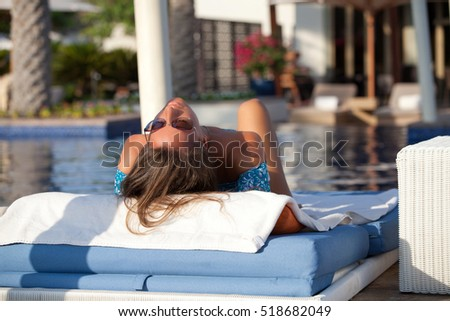 Beautiful women relaxing near pool. Lady day dreaming and sunbathing, looking happy. Summer luxury vacation.