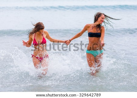 Beautiful women running in the waters holding hands of the Mediterranean sea infused with happiness.