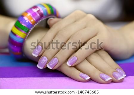 Beautiful women's manicure with purple polish on the nails - stock photo