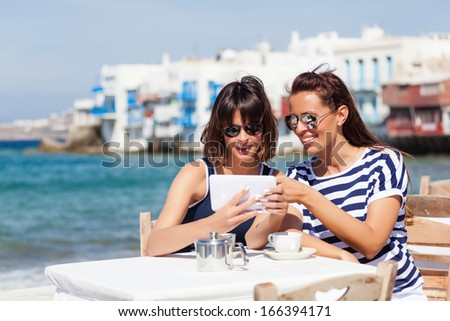 Beautiful women sitting at a seaside cafe,drinking a coffee and using a digital tablet - stock photo