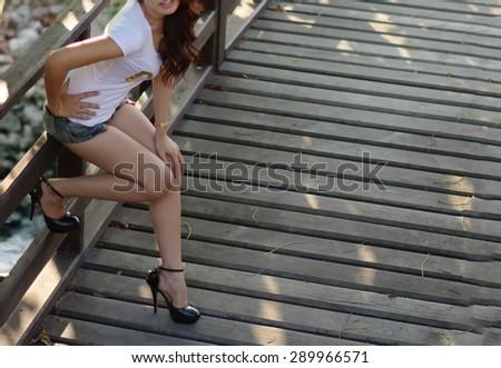 beautiful women sitting on a wooden railing. - stock photo