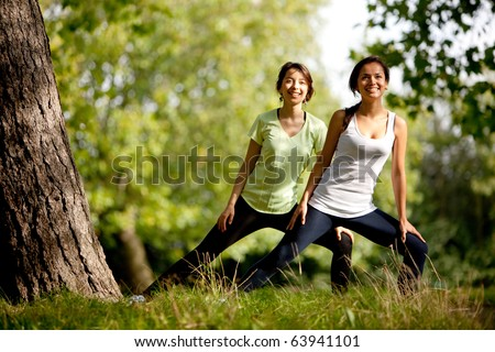 Beautiful women stretching at the park - fitness concepts - stock photo