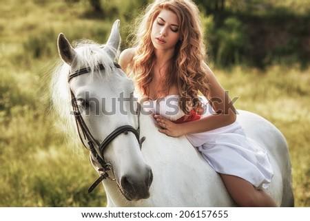 Beautiful women wearing white dress riding on white horse  - stock photo
