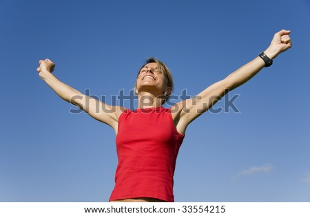 Beautiful women with her arms outstretched on a blue sky - stock photo