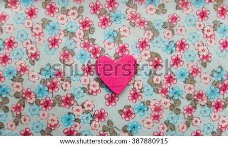 Beautiful wood sewing button scrap-booking heart shaped love pink on a delicate floral background, background flowers for postcard, place for text. Figure heart wood handmade - stock photo
