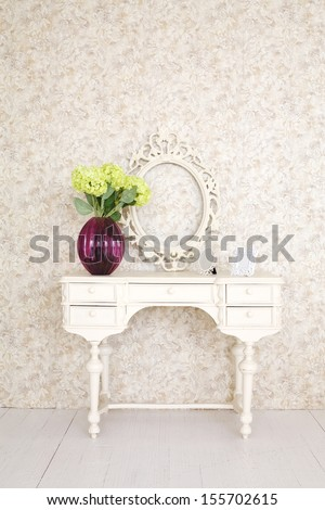 Beautiful wooden carved dressing table with blank frame in light room. - stock photo