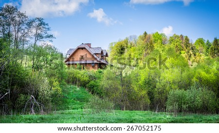 Beautiful wooden cottage on a hill somewhere in forest - stock photo