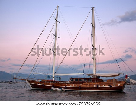 Beautiful wooden luxury yacht in the sea at sunset