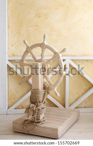 Beautiful wooden ship wheel with wire rope in light room with yellow walls. - stock photo