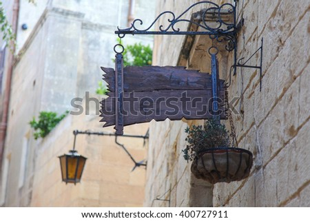 Beautiful wooden sign over building entrance in old town - stock photo