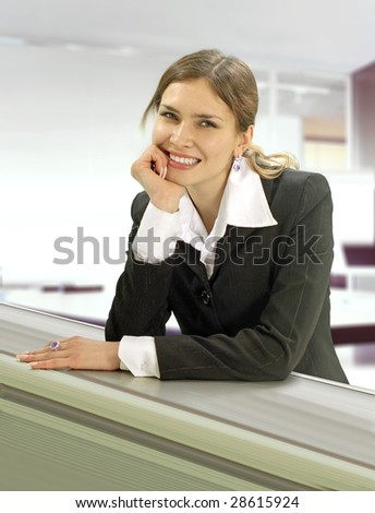 beautiful wooman stands near the desk in commercial company - stock photo