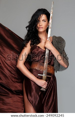 Beautiful woomen with black hair hold sword near her chest. Dark-red dress, chain armor. Isolated on grey background. - stock photo