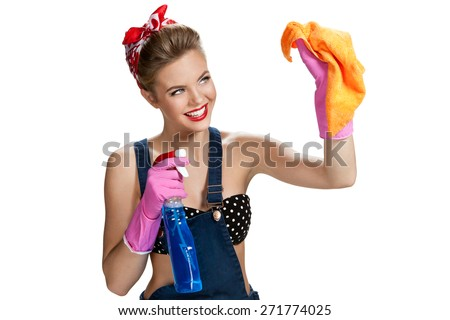 Beautiful worker wearing pink rubber protective gloves holding cleaning spray bottle and orange microfiber cloth / young beautiful pin-up girl isolated on white background. Cleaning service concept - stock photo