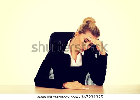 Beautiful worried businesswoman behind the desk - stock photo