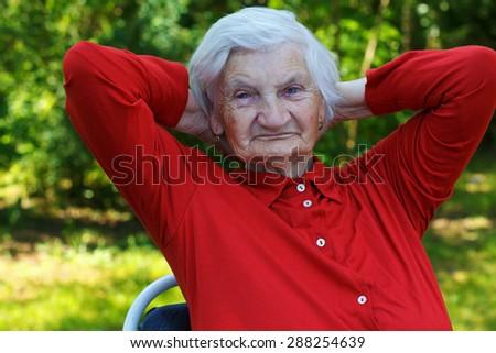 Beautiful wrinkled elderly woman relaxing in the garden - stock photo