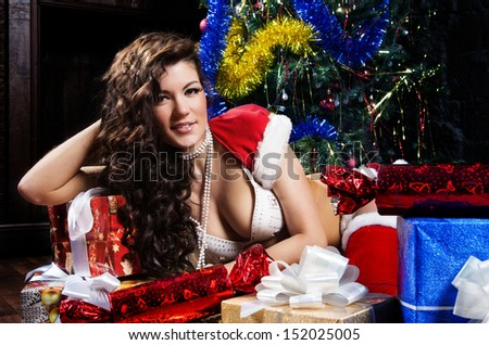 Beautiful xmas brunette as snow maiden near the new year tree and gift boxes