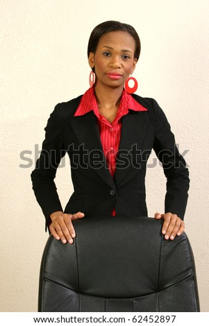Beautiful 25 year old african american woman in suit behind office chair. - stock photo