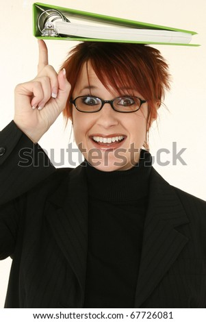 Beautiful 30 year old business woman in black suit balancing green binder on head with happy expression. - stock photo