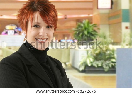 Beautiful 30 year old business woman in black suit with smiling  expression in hotel lobby.