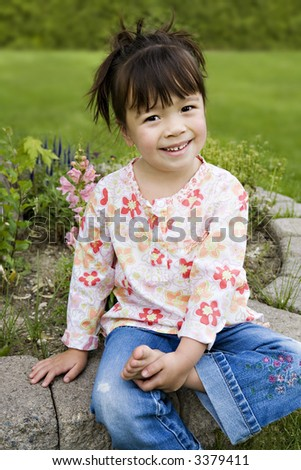 Beautiful 3-Year-Old Girl with a Happy Expression in her Backyard - stock photo