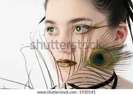 Beautiful 13 year old girl with with green eyes and feathers. - stock photo