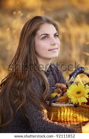 Beautiful 20 year old woman enjoying an autumn day outdoors. - stock photo