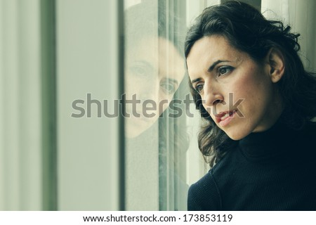 beautiful 35 year old woman stands in front of the window - stock photo