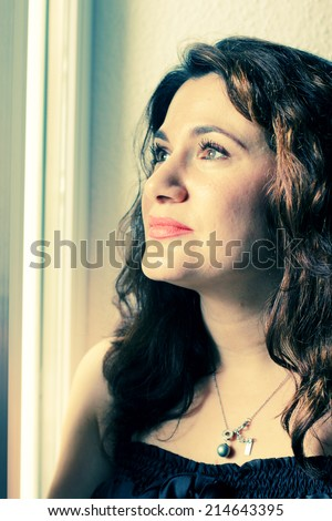 beautiful 35 year old woman stands near the window - stock photo