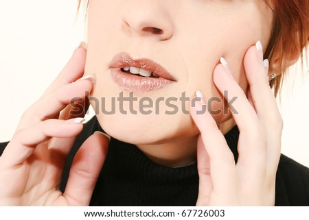 Beautiful 30 year old woman with attractive manicured hands on face.