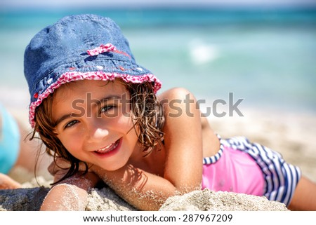 Beautiful 5 years old girl laying and smiling on the beach. - stock photo