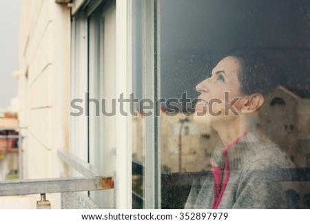 beautiful 40 years old woman looking through the window