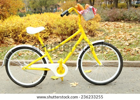 Beautiful yellow bicycle in autumn park with tasty bread in basket - stock photo