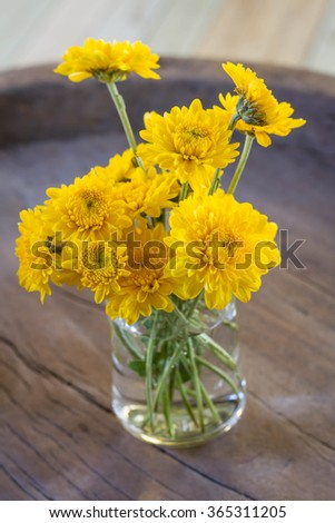 Beautiful yellow Chrysanthemum flower in glass bottle with brown rope on old wooden table