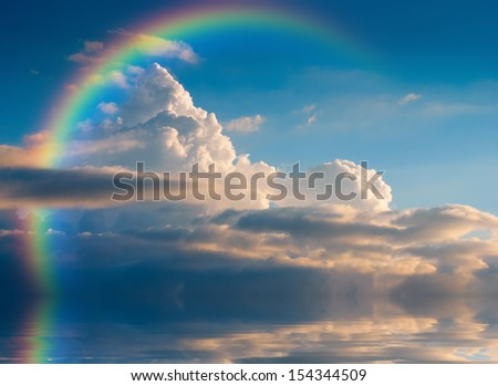 Beautiful yellow clouds with rainbow, reflected in a river - stock photo