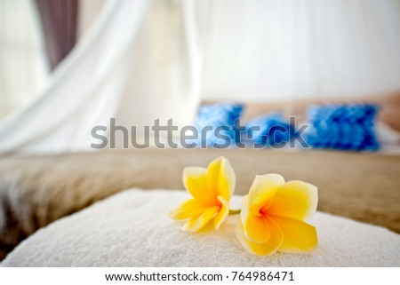 Beautiful yellow flowers placed on a white towel in a white and blue furnished modern bedroom